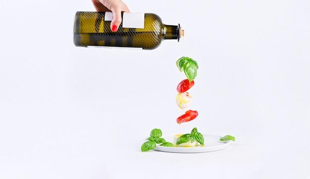 Vrouwelijke hand met fles olie en vliegende salade in het frame. traditionele italiaanse caprese salade. tomaten, mozzarella, basilicum, olijfolie