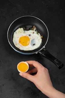 Vrouwelijke hand met gebroken ei op zwarte ondergrond.