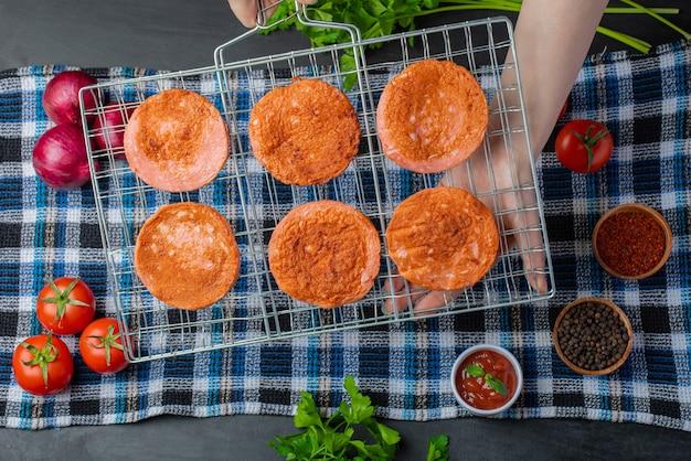 Vrouwelijke hand met gegrilde salami plakjes op grill rooster over verse groenten.