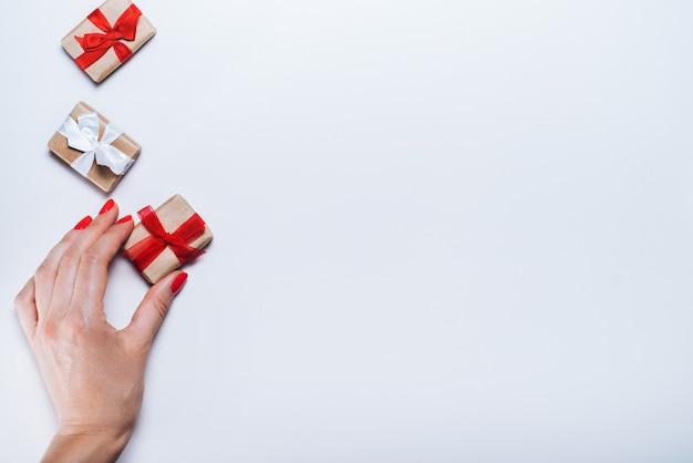Vrouwelijke hand met geschenkdoos met rood lint op lege witte achtergrond