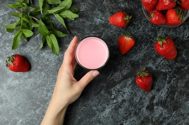 Vrouwelijke hand met glas aardbeienmilkshake op zwarte rokerige achtergrond