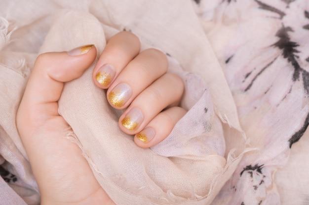 Vrouwelijke hand met gouden glitter nagel ontwerp.