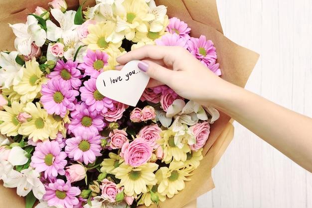 Vrouwelijke hand met hartvormige wenskaart met tekst i love you boven boeket van roze en gele bloemen.