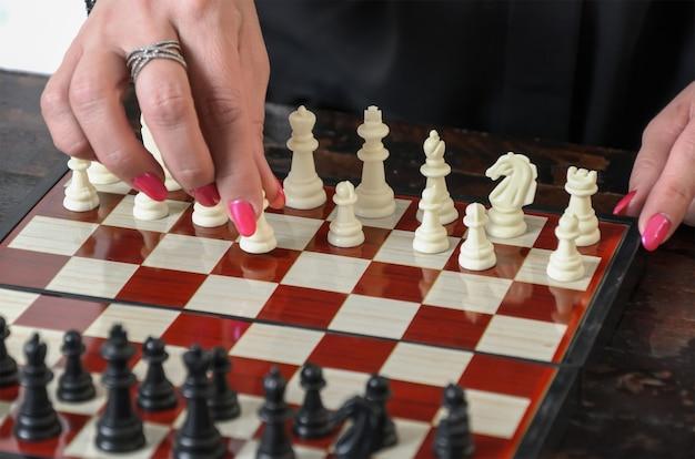 Vrouwelijke hand met heldere manicure houdt witte pion aan het begin van het schaakspel