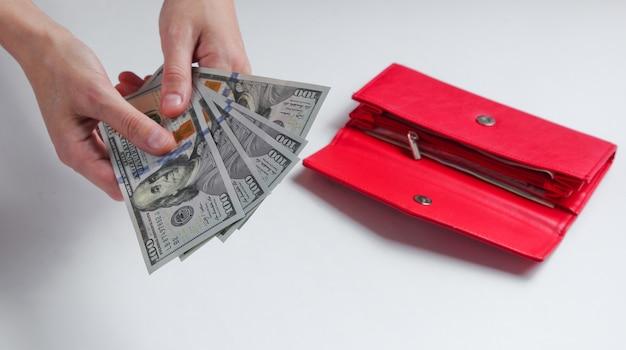 Vrouwelijke hand met honderd-dollarbiljetten op wit met een rode portemonnee.