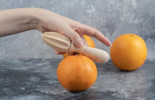 Vrouwelijke hand met houten knijpgereedschap op marmeren tafel.