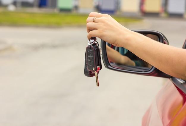 Vrouwelijke hand met in hand autosleutel, vage achtergrond