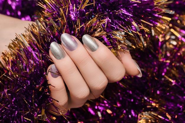 Vrouwelijke hand met kerst nageldesign.