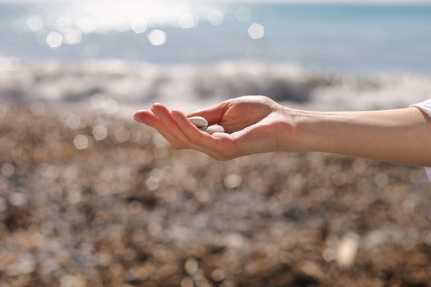 Vrouwelijke hand met kleine kiezelstenen in de hand in de buurt van blauwe zee op een strand, kiezels oppakken op het stenen strand, ronde vorm kiezels, zomer vakantie souvenir, stranddag, selectieve aandacht