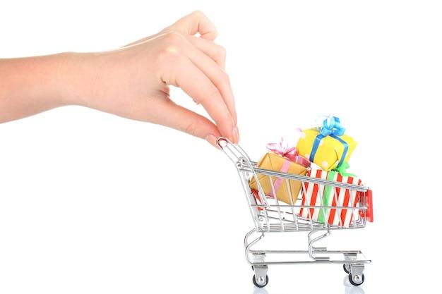 Vrouwelijke hand met kleine winkelwagen vol geschenken, geïsoleerd op wit