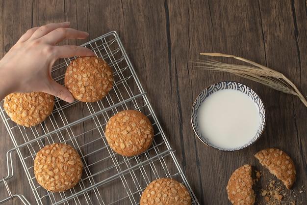 Vrouwelijke hand met koekje in de buurt van kom verse melk op houten tafel