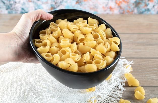 Vrouwelijke hand met kom vol droge pasta op houten tafel.