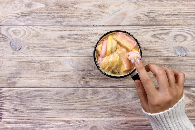 Vrouwelijke hand met kop warme chocolademelk of chocolade met marshmallow op hout