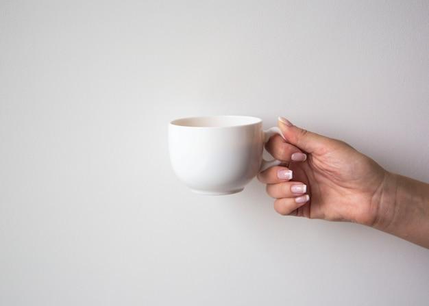 Vrouwelijke hand met kopje koffie