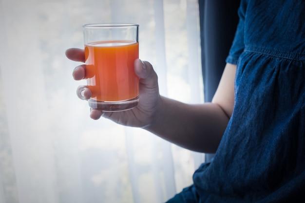 Vrouwelijke hand met kopje sinaasappelsap in de ochtend als ze wakker wordt. gezonde levensstijl conceptideeën