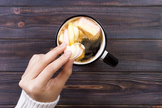Vrouwelijke hand met kopje warme chocolademelk of chocolade met marshmallow op houten tafel van bovenaf
