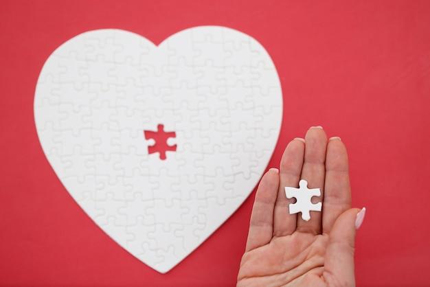 Vrouwelijke hand met laatste stuk van puzzels in de vorm van hart close-up