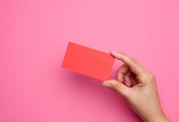 Vrouwelijke hand met leeg rood papier op een roze achtergrond. kopieer en plak afbeelding of tekst, close-up