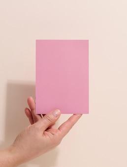 Vrouwelijke hand met leeg roze papier op een beige achtergrond. kopieer en plak afbeelding of tekst, close-up