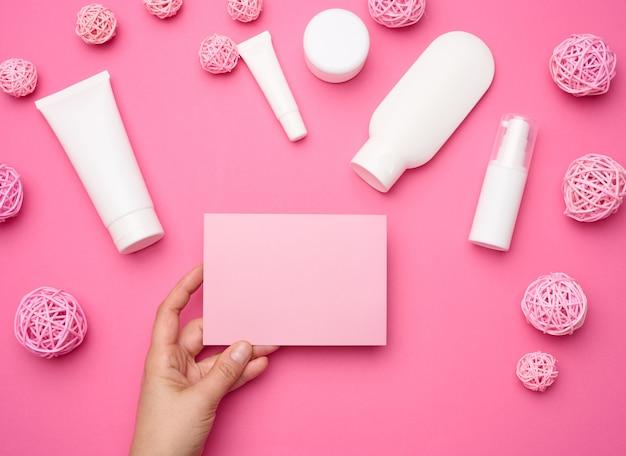 Vrouwelijke hand met leeg roze papier op een roze achtergrond en pot, fles en lege witte plastic buizen voor cosmetica. verpakking voor crème, gel, serum, reclame en productpromotie, mock-up