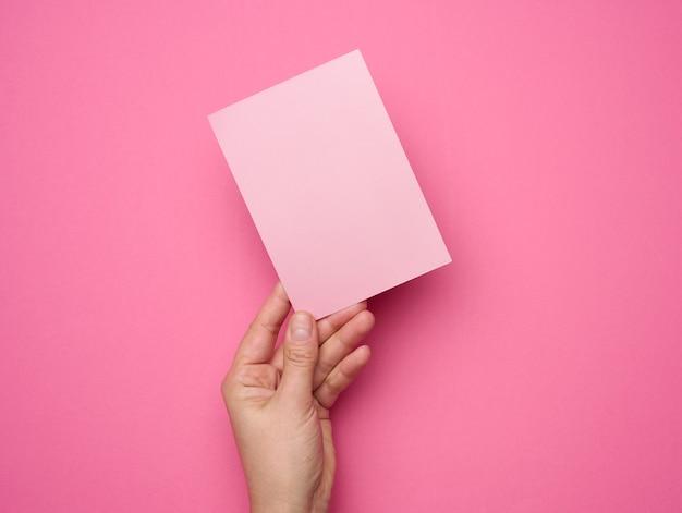 Vrouwelijke hand met leeg roze papier op een roze achtergrond. kopieer en plak afbeelding of tekst, close-up