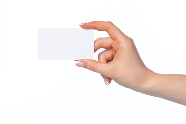 Vrouwelijke hand met leeg wit adreskaartje dat op wit wordt geïsoleerd