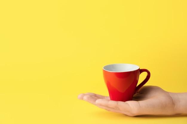 Vrouwelijke hand met lege kop op kleur