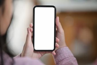Vrouwelijke hand met lege witte scherm mobiele telefoon over wazig bokeh achtergrond
