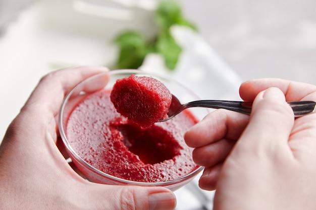 Vrouwelijke hand met lepel met aardbeienmousse