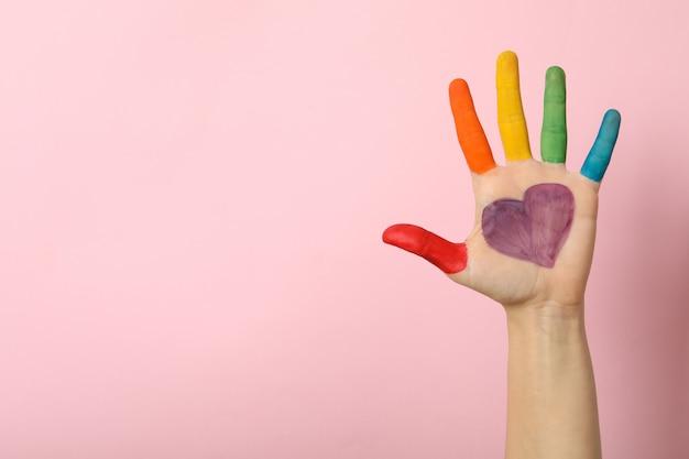 Vrouwelijke hand met lgbt-kleuren op roze