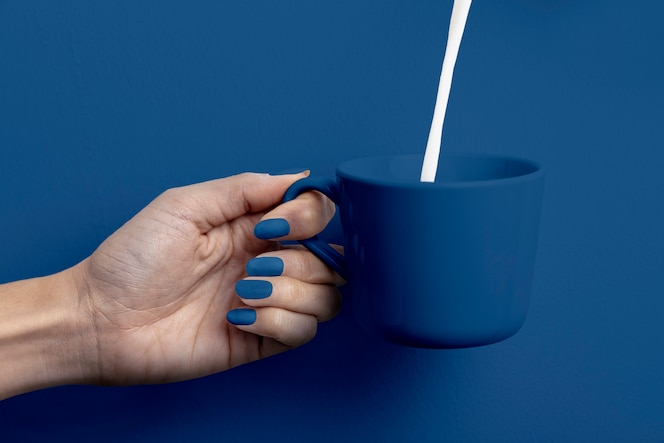 Vrouwelijke hand met melk cup