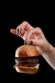 Vrouwelijke hand met minihamburger als kerstboomspeelgoed op zwarte achtergrond.