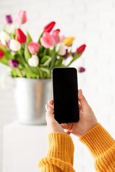 Vrouwelijke hand met mobiele telefoon die foto van tulpenbloemen houdt
