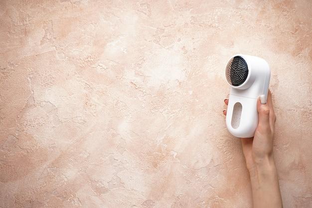 Vrouwelijke hand met moderne stof scheerapparaat op kleur achtergrond, plaats voor tekst. bovenaanzicht.
