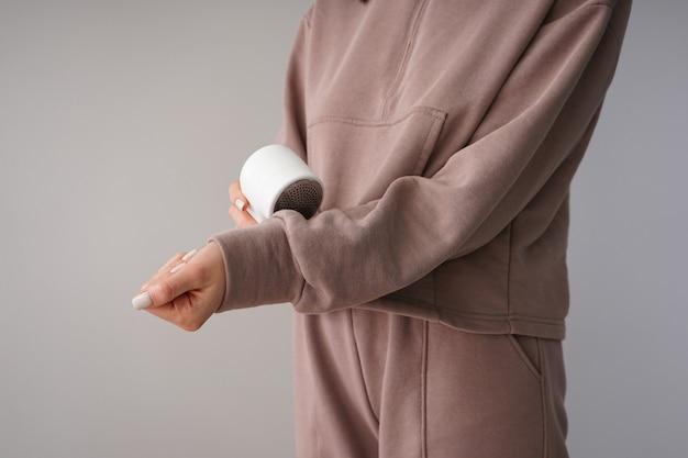 Vrouwelijke hand met moderne stoffen scheerapparaat en trui op een grijze achtergrond.
