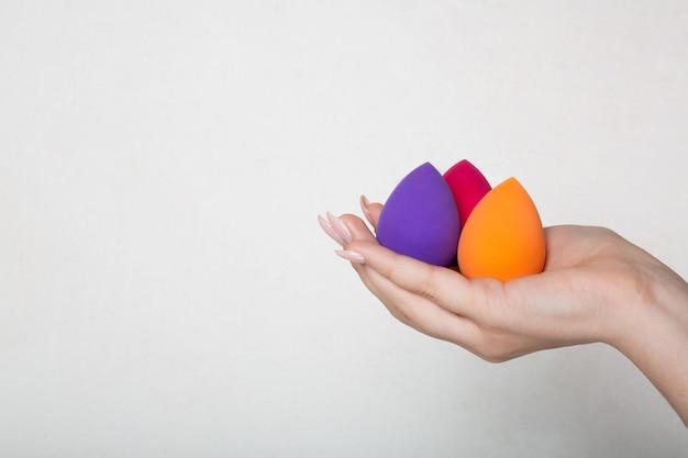 Vrouwelijke hand met mooie manicure met paarse, roze en oranje beautyblenders