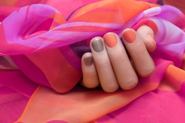 Vrouwelijke hand met oranje en grijs nagelontwerp.