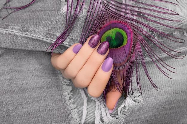 Vrouwelijke hand met paars nageldesign met pauwenveer op denim oppervlak.