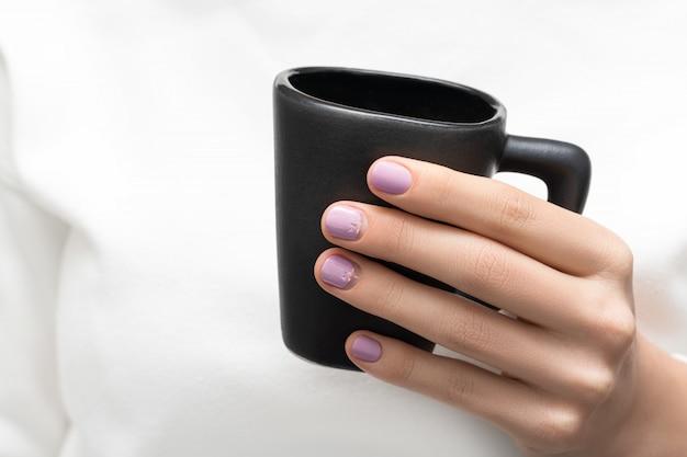 Vrouwelijke hand met paars spijkerontwerp dat zwarte koffiekop houdt