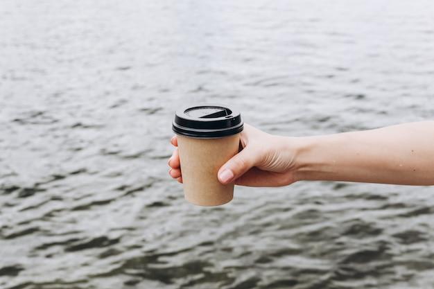 Vrouwelijke hand met papieren beker. vrouwelijke hand met een kopje koffie. kopieer ruimte