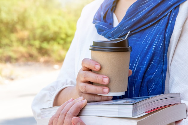 Vrouwelijke hand met papieren kopje koffie meenemen, papieren koffiekopje in handen van vrouwen met perfecte manicure