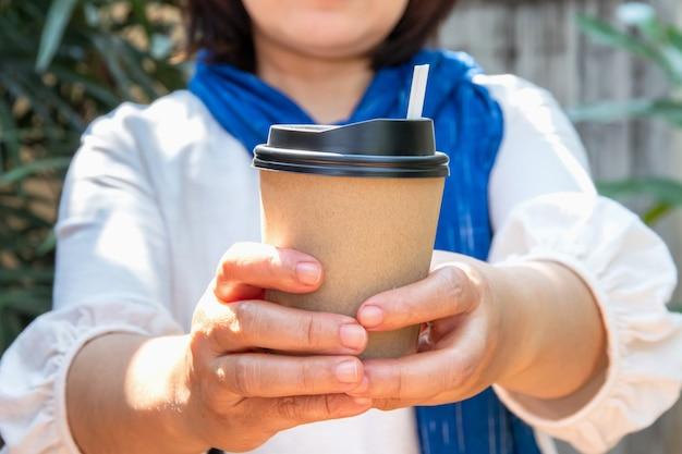 Vrouwelijke hand met papieren kopje koffie meenemen, papieren koffiekopjes in handen van vrouwen met perfecte manicure