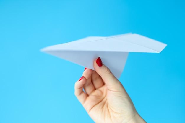Vrouwelijke hand met papieren vliegtuigje op blauwe achtergrond