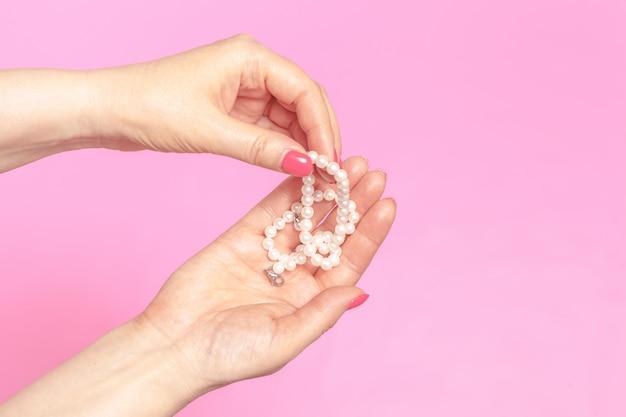 Vrouwelijke hand met parels op roze