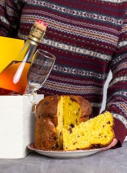 Vrouwelijke hand met pasen panetone italiaans stuk dichtbij leveringsdoos met champagnefles.