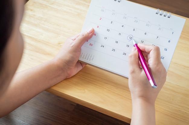 Vrouwelijke hand met penteken op kalender