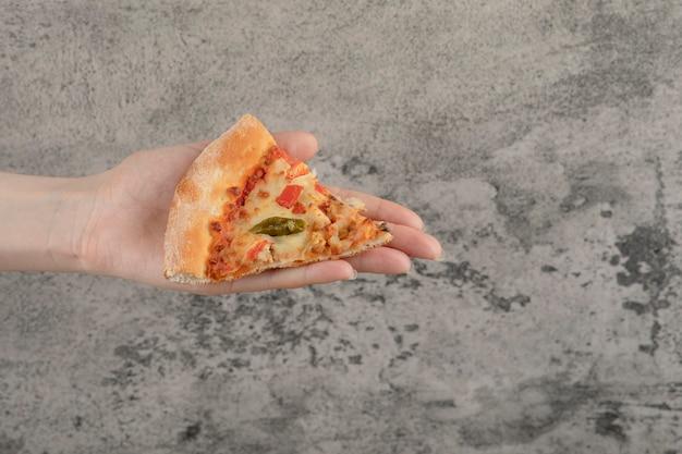 Vrouwelijke hand met plak van smakelijke pizza op stenen achtergrond.
