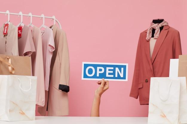 Vrouwelijke hand met plakkaat met open teken in de kledingwinkel