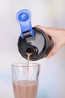 Vrouwelijke hand met plastic shaker met proteïne shake en glas op lichte achtergrond