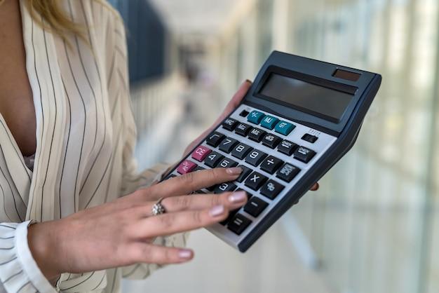 Vrouwelijke hand met rekenmachine in moderne zakencentrum